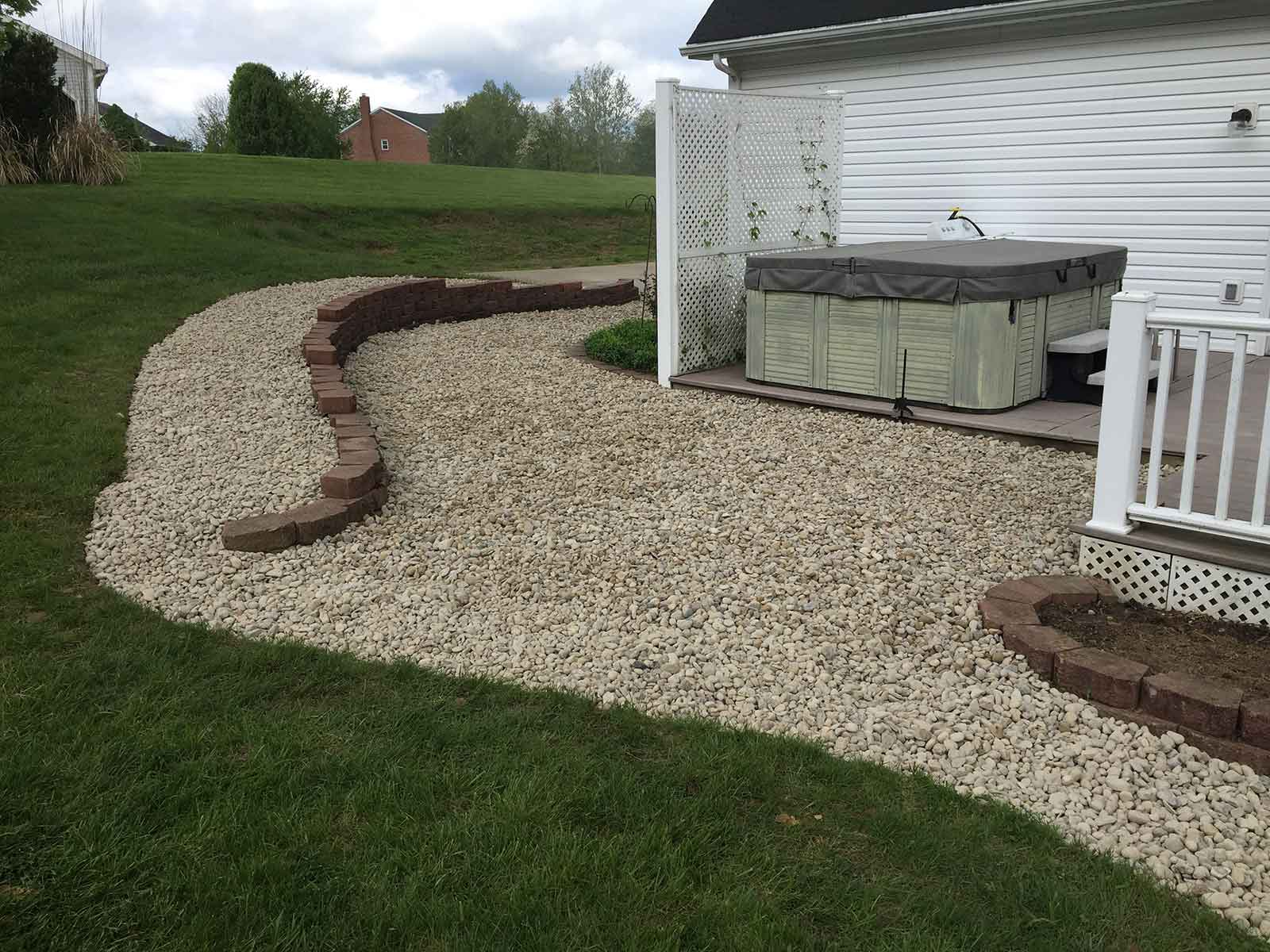 backyard landscaping with hot tub, retraining wall, and stone